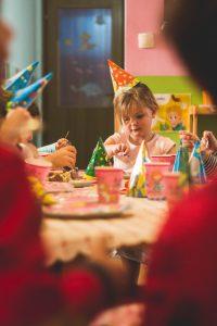Anniversaire d'une petite fille, à table avec ses invités devant son gâteau