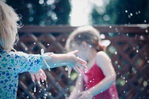 Petites filles jouant avec de l'eau dans un jardin